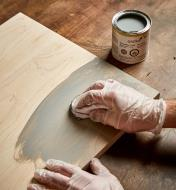 Using a cloth to apply Osmo silk gray wood wax to a wood surface