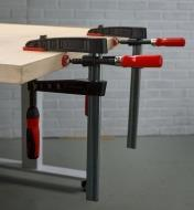 Two Bessey single-spindle edge clamps used with a Bessey fast-acting clamp used to clamp a strip of wood to the edge of a panel