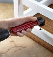 Using the 90° screwdriving attachment to drive a screw between a chair seat and rung