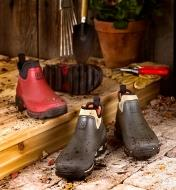 Pair of red and pair of green Gardener's Shoes sitting on a doorstep with garden tools and gloves.