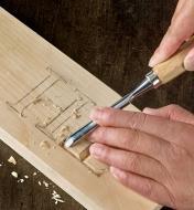 Personne sculptant une lettre dans une pièce de bois avec une gouge du jeu de sept outils de sculpture pour fabriquer une enseigne