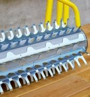 Gros plan des dents en acier galvanisé d'un râteau rotatif pour plan d'eau montrant leur forme de crochet