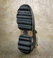 A close view of the underside of a gardener's shoe, showing the widely spaced treads