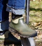 A gardener digs into the ground with a shovel while wearing a pair of gardener's shoes