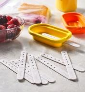 Several ice pop sticks lying in front of ice pop molds and a bowl of raspberries