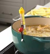 The candy and deep-fry thermometer clipped to a pot of deep-frying potato strips