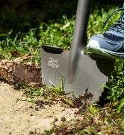 A close view of the root-cutter lawn edger's blade penetrating the soil