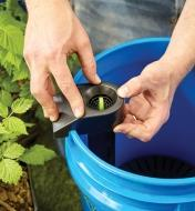 Clipping a bracket with a green tab in its center to the top of the bucket
