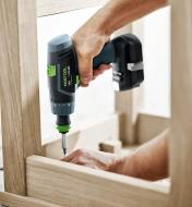 Driving a screw into the underside of a chair with TXS Cordless Drill