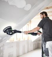 A worker sands an angled wall with the Planex LHS 2 225