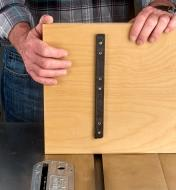 A woodworker installs a sliding jig on a table saw using a single Zeroplay miter bar