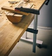 """A Bessey 7"""" medium-duty FA clamp clamping a halved log to a workbench"""