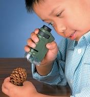 A child uses the Pocket Microscope to look at a pine cone