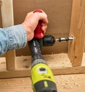 Boring a hole in a wall stud using the 90° drilling attachment on a standard drill