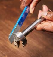 Personne utilisant un petit affiloir diamanté EZE-Lap pour affûter une mèche à arêtes dentées
