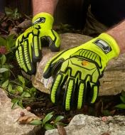 A landscaper wears impact-resistant gloves while positioning a large rock in a garden