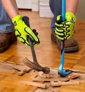 A renovator wears impact-resistant gloves while removing hardwood flooring with a hammer and pry bar