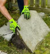 A landscaper wears impact-resistant gloves while removing an old, cracked patio stone