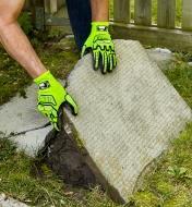 Personne munie de gants antichocs soulevant une vieille dalle de terrasse fissurée