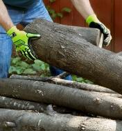 Personne munie de gants antichocs empilant du bois de chauffage
