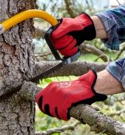 A person wears a pair of Universal-Fit gloves while using a bow saw to cut a limb from a tree