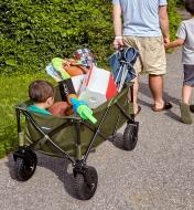 Homme tirant un enfant, une glacière et différents objets dans un chariot pliant