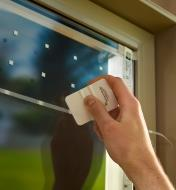 Pressing a line of tape against a window with a plastic card