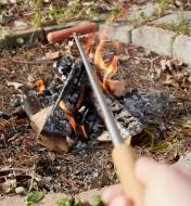 Cooking a hot dog over a campfire using the telescoping campfire fork