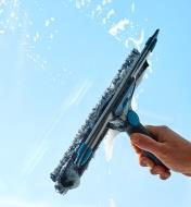 Using the scrubber side of the tool to wash a window