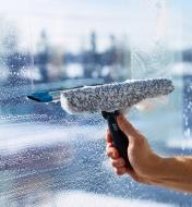 Using the squeegee side of the tool to clear soapy water from a window
