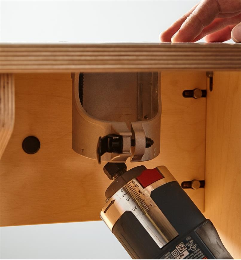 Removing a compact router to change bits without separating the sleeve and base plate from the table