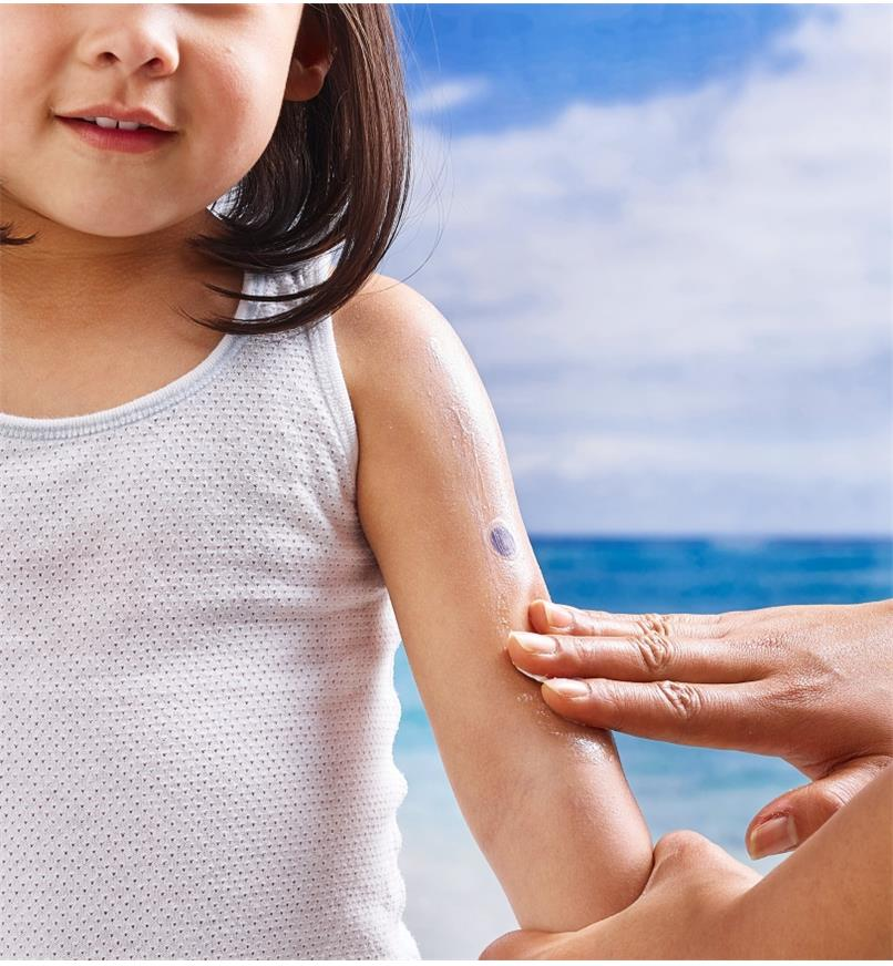 Applying sunscreen lotion over a purple Spot My UV (UV detection sticker) adhered to exposed skin