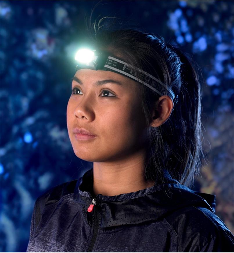 Attached to a headband, the multi-function LED headlamp is positioned on the forehead