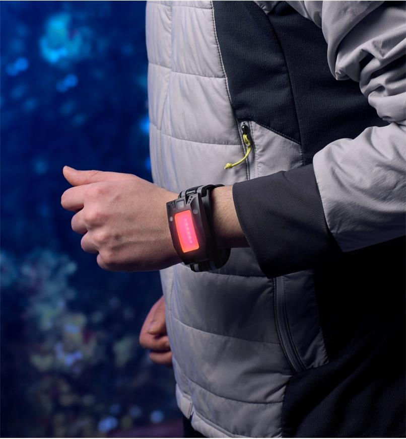 The multi-function LED headlamp is worn on a runner's wrist