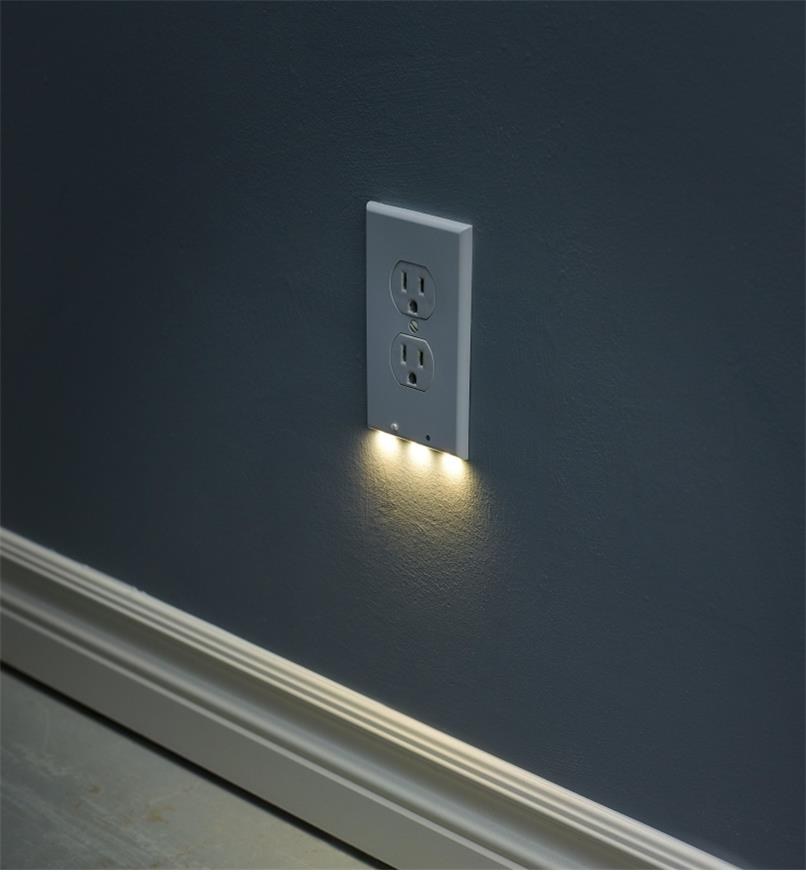 A duplex-style LED outlet cover plate mounted on a wall, giving gentle, diffused lighting at night.