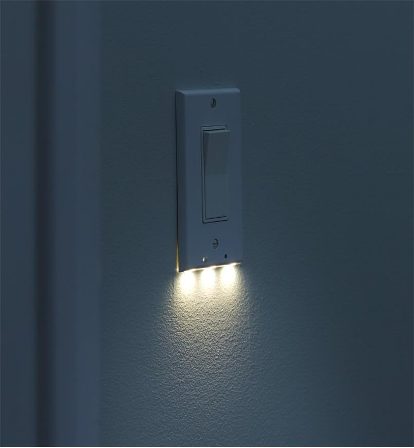 An LED rocker switch cover plate mounted on a wall, giving gentle, diffused illumination at night.