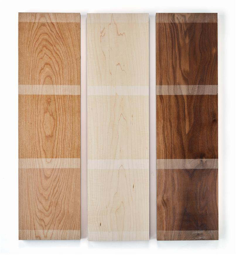 Blocks of cherry, maple and walnut wood with examples of matte, satin and satin pigmented finishes