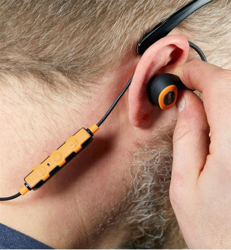 A man inserts an ISOtunes Pro 2.0 corded electronic hearing protector earbud into his ear