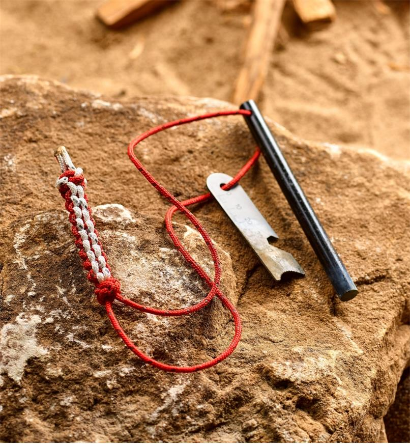 The firestarter rod and multi-tool striker threaded onto a braided lanyard