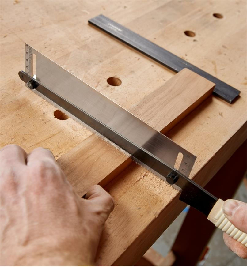 An adjustable-depth dozuki being used to make a cut in a thin piece of wood