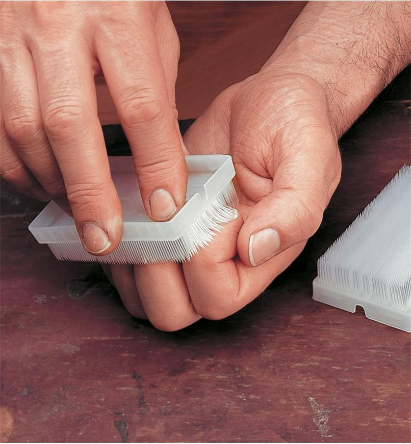 Nail brush being used to clean fingernails