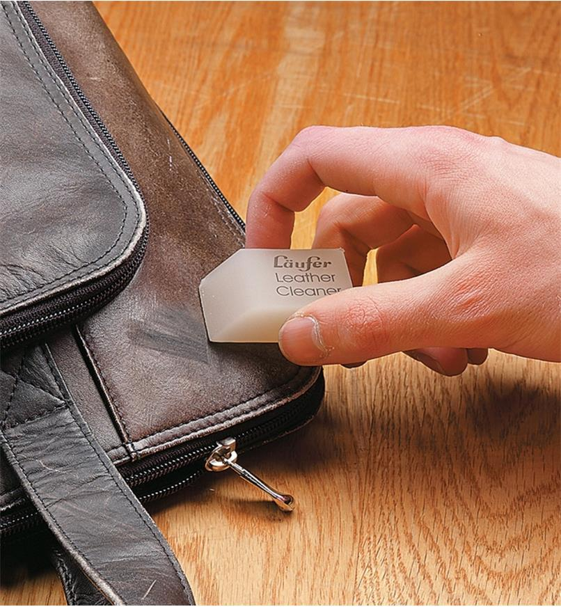 Using the leather eraser to clean a briefcase
