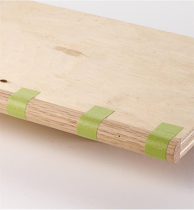 Using binding tape to hold a hardwood bullnose molding in place on the front of a plywood shelf while the glue dries
