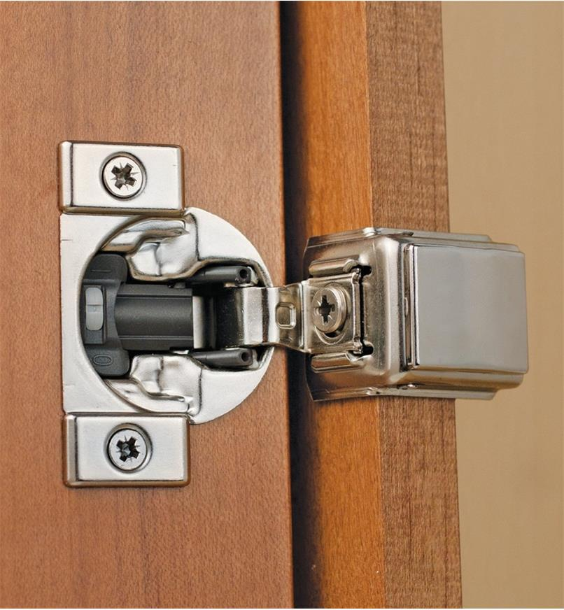 Compact Blumotion 110° Overlay Hinge installed in a cabinet door