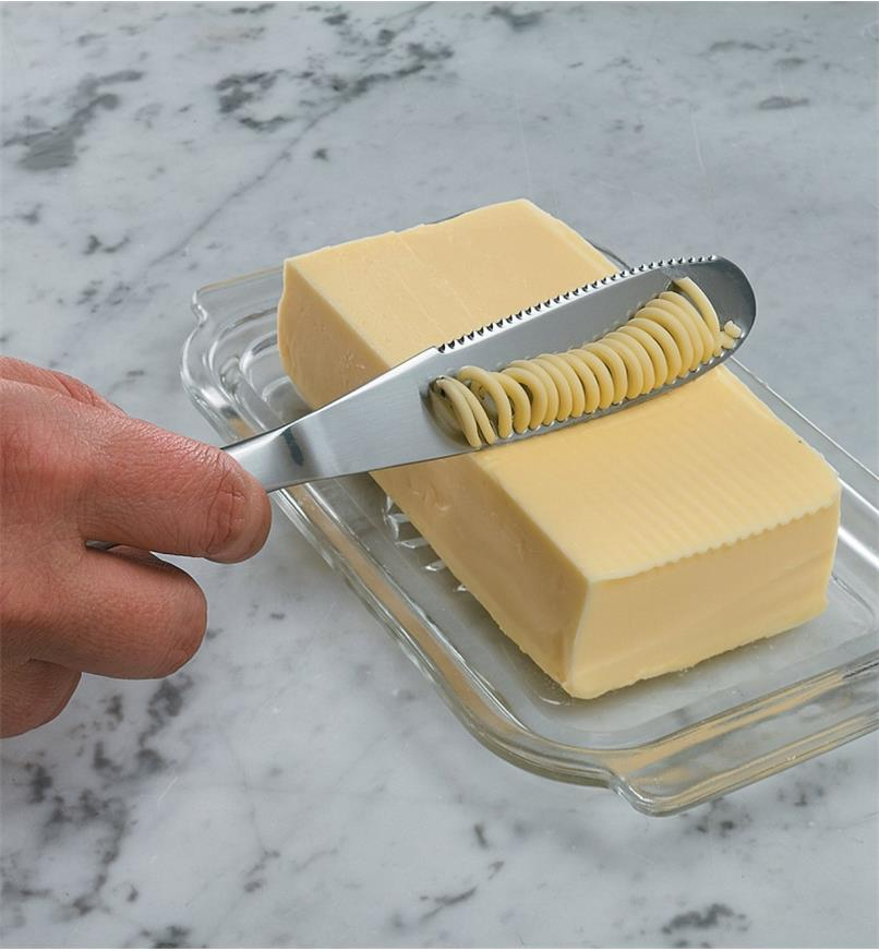 Drawing the knife across a block of butter, creating thin ribbons