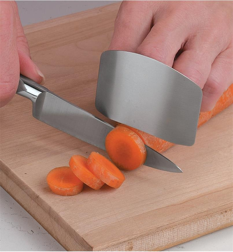 Using the Chop-Safe Finger Guard to protect the fingers while chopping a carrot