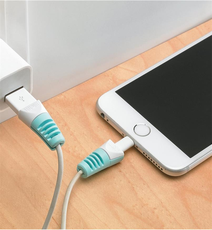 An iPhone plugged into a charger with cable savers on either end of the cable