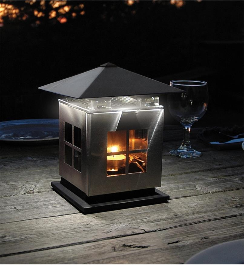 Candle-Powered LED Lantern on an outdoor table with the roof lowered to illuminate a localized area