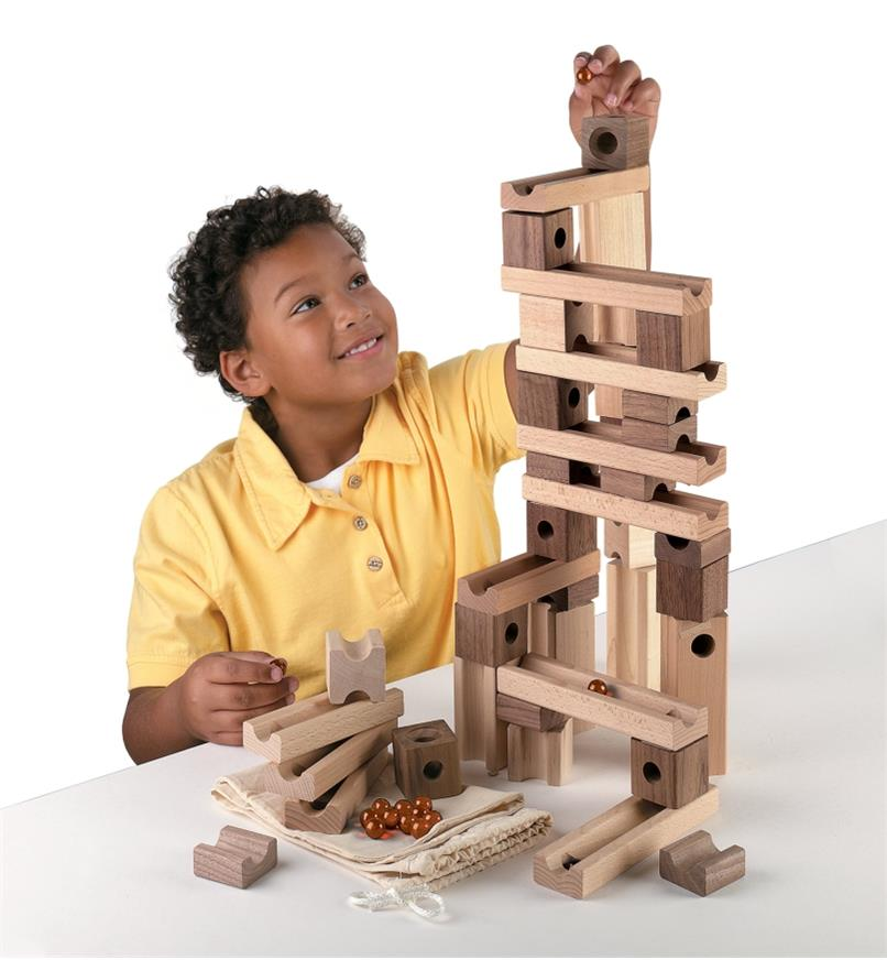 A boy about to place a marble in the top of a marble run