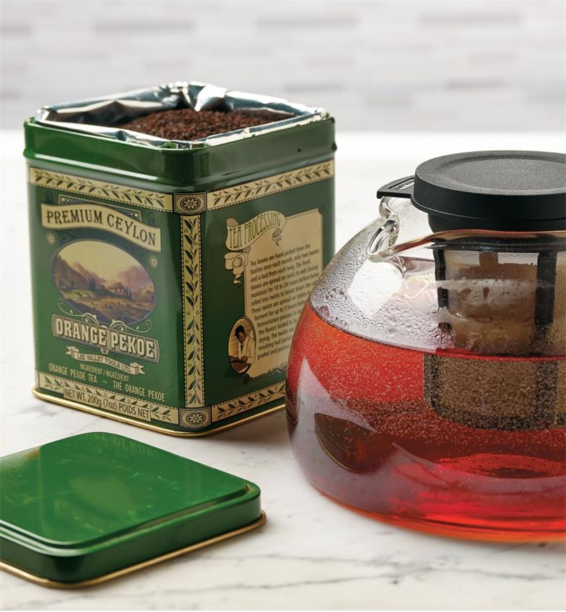 A tin of Orange Pekoe Tea beside a glass teapot with tea brewing inside